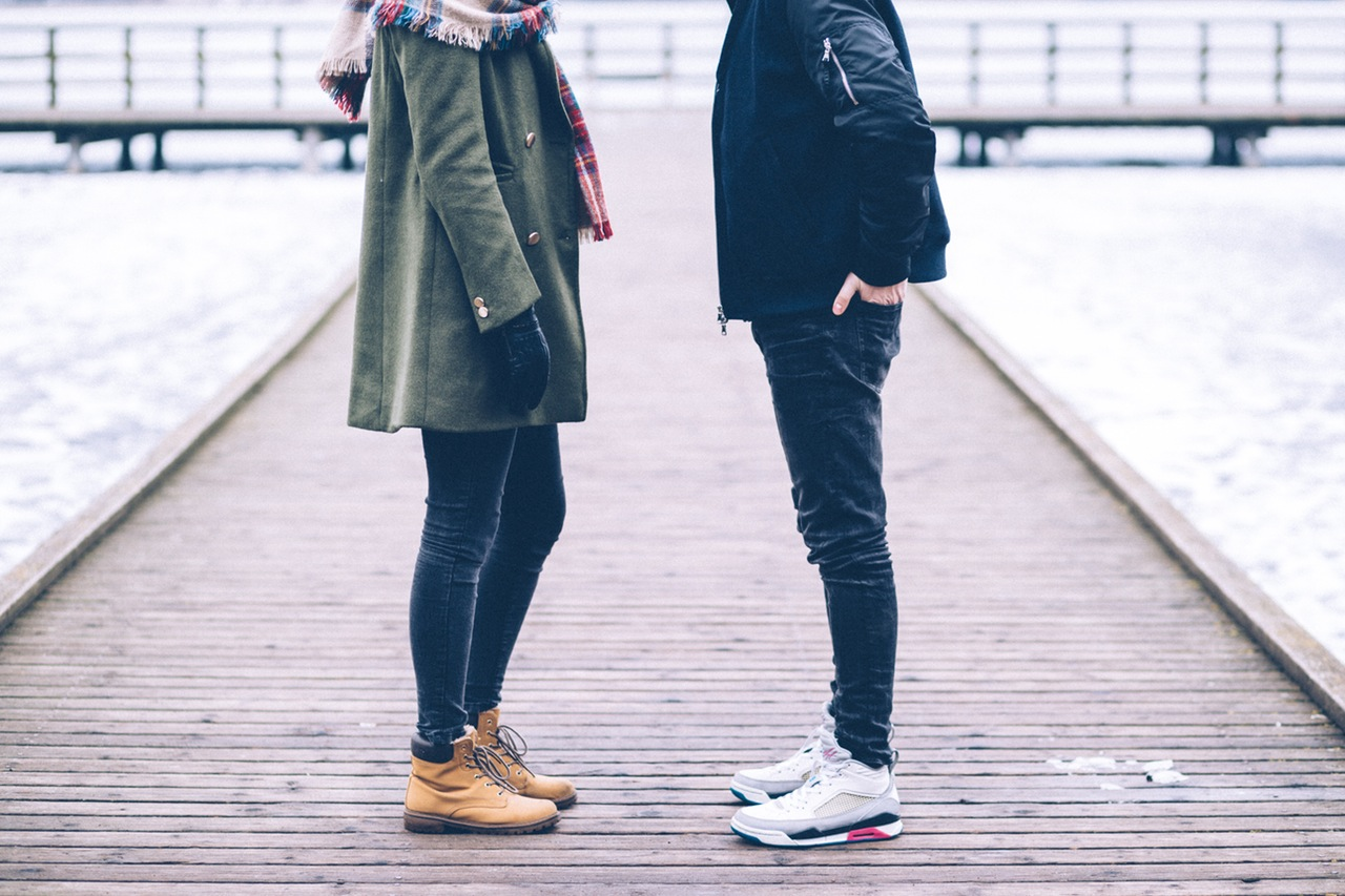 A guy and a girl are standing outside